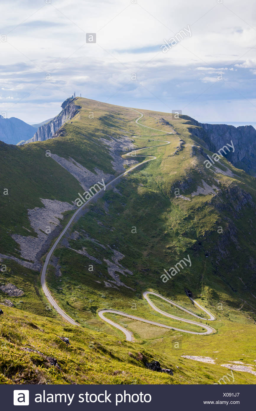 Steep road of curves on green meadows framed by rocky peaks Sorland Vaeroy Island county of Nordland Lofoten Norway Europe - Stock Image