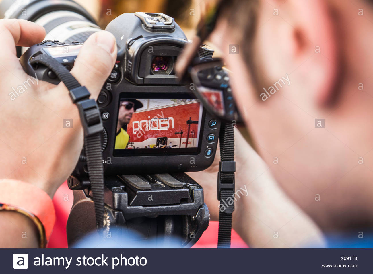 Close up of photographer checking photograph of mountain biker on camera - Stock Image