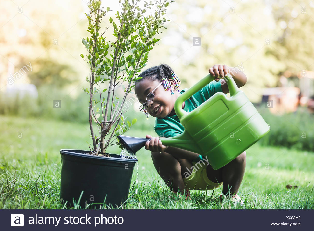 Girl watering plant in parkland eco camp - Stock Image