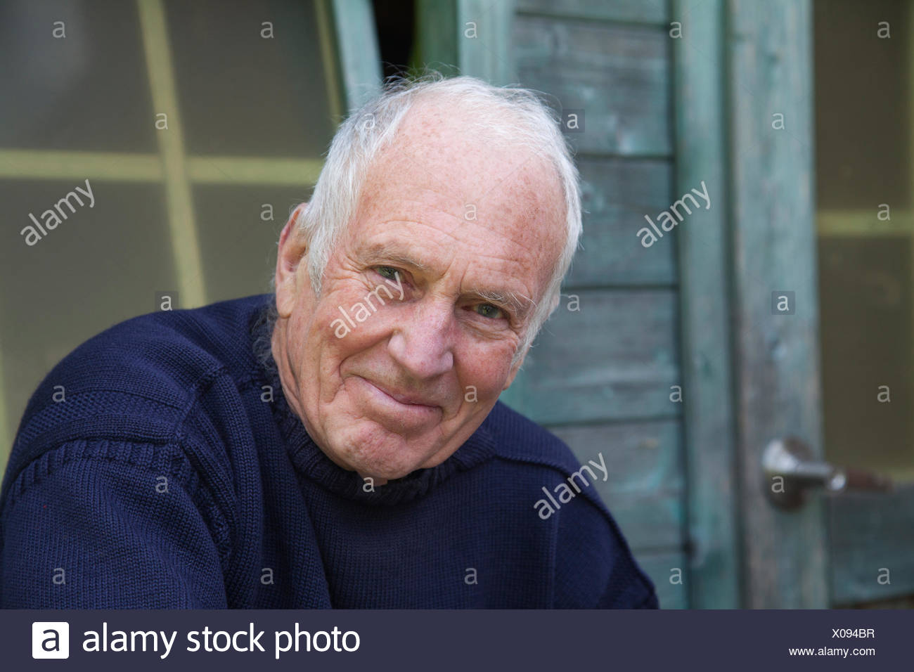 Senior man sitting, relaxing, outside shed - Stock Image