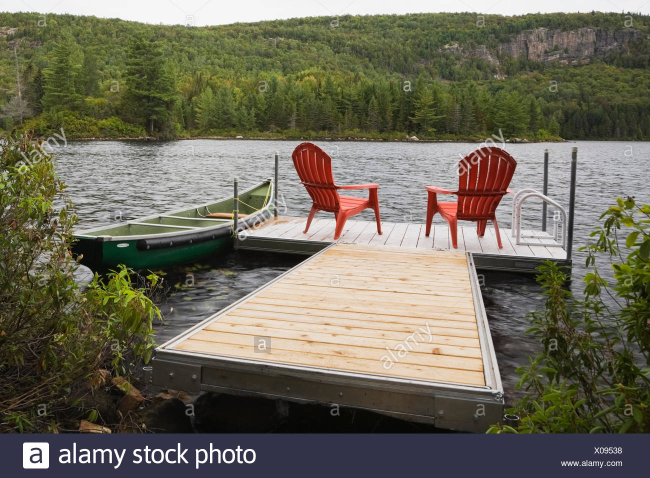 Two Red Adirondack Chairs On Floating Dock On River