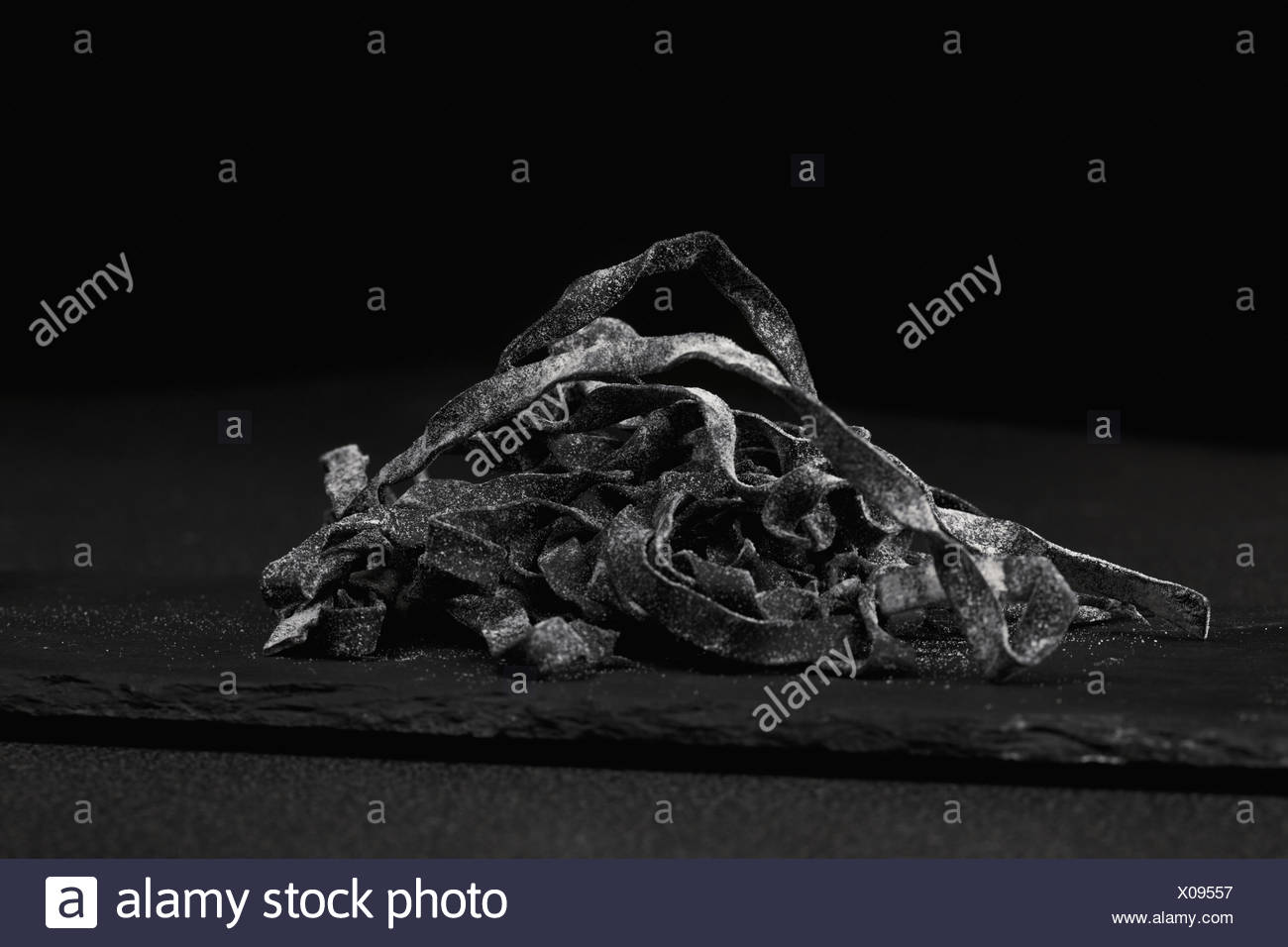 Black noodles in a darkness - Stock Image