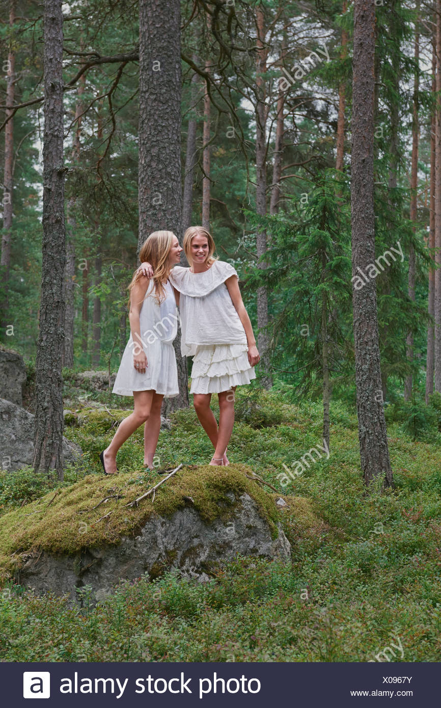 Teenage girls standing on rocks in forest - Stock Image