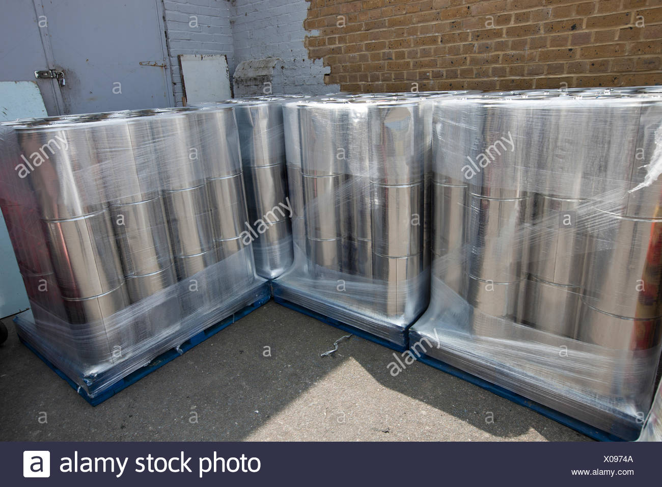 Stack of tins outside warehouse - Stock Image