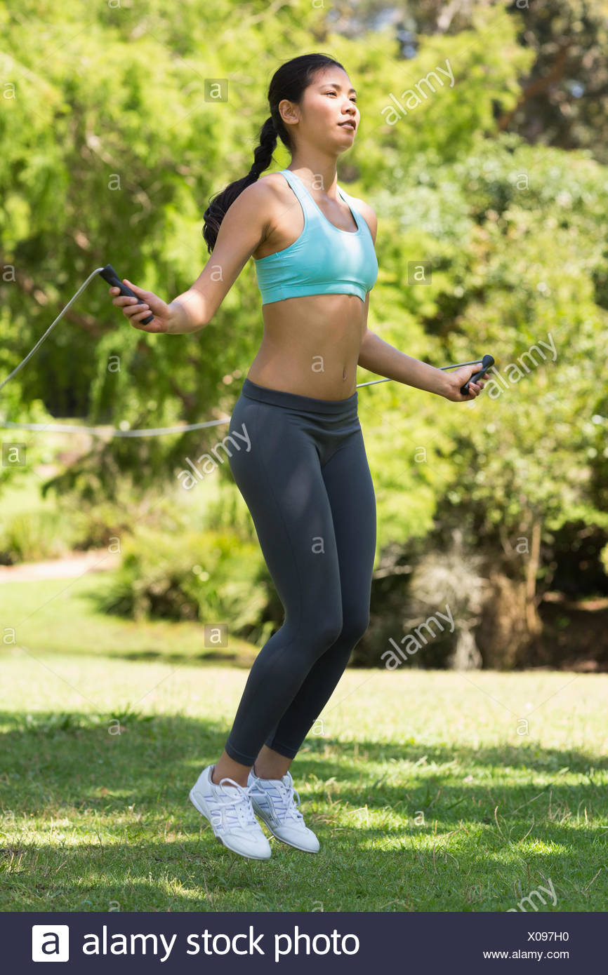 Healthy and beautiful woman skipping in park - Stock Image