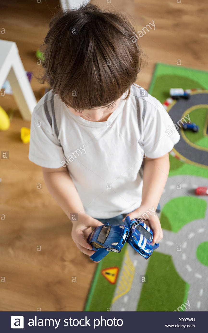 Boy (4-5) playing with cars - Stock Image