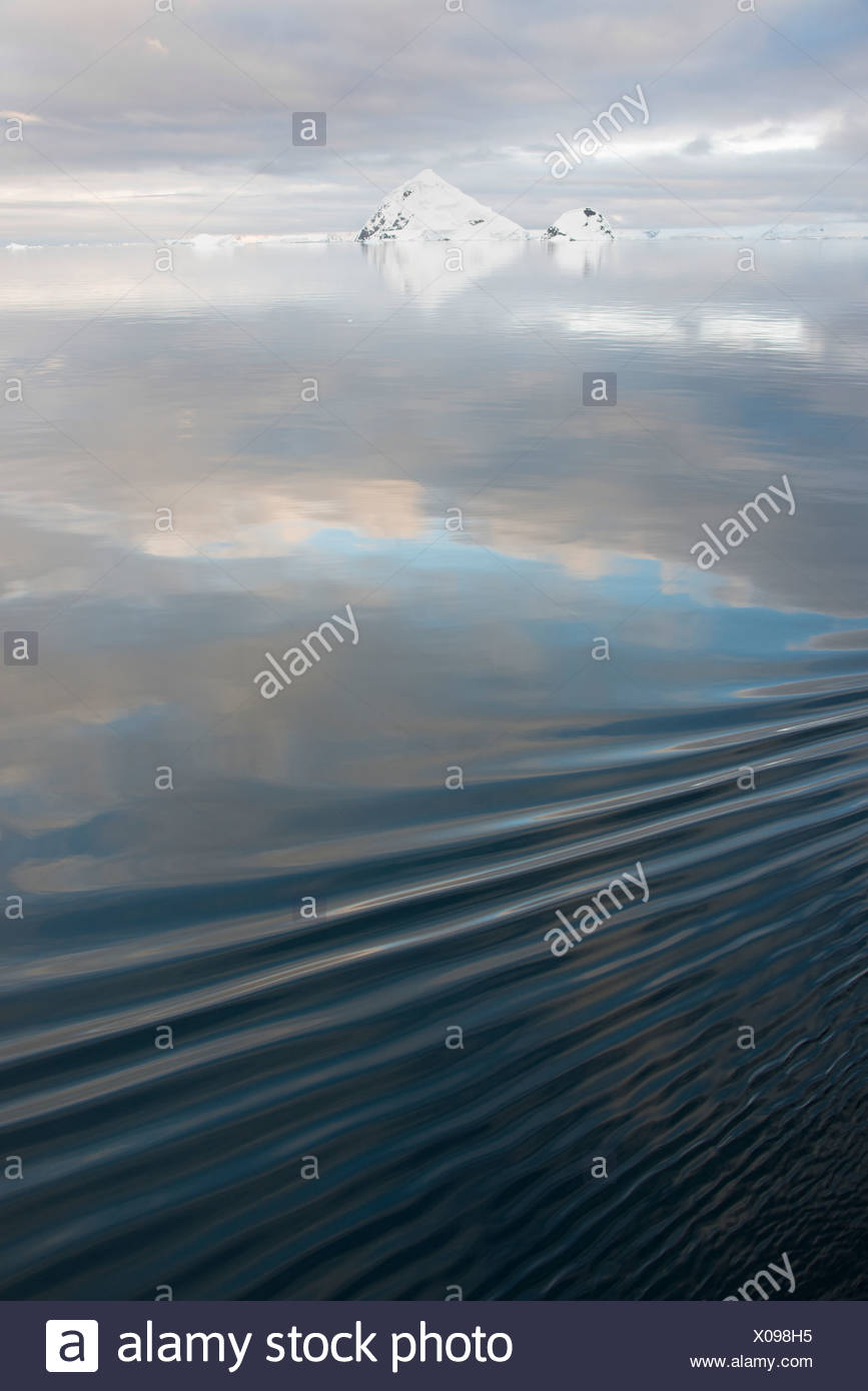 Mountains covered in snow, reflected in the calm waters of the ocean. - Stock Image