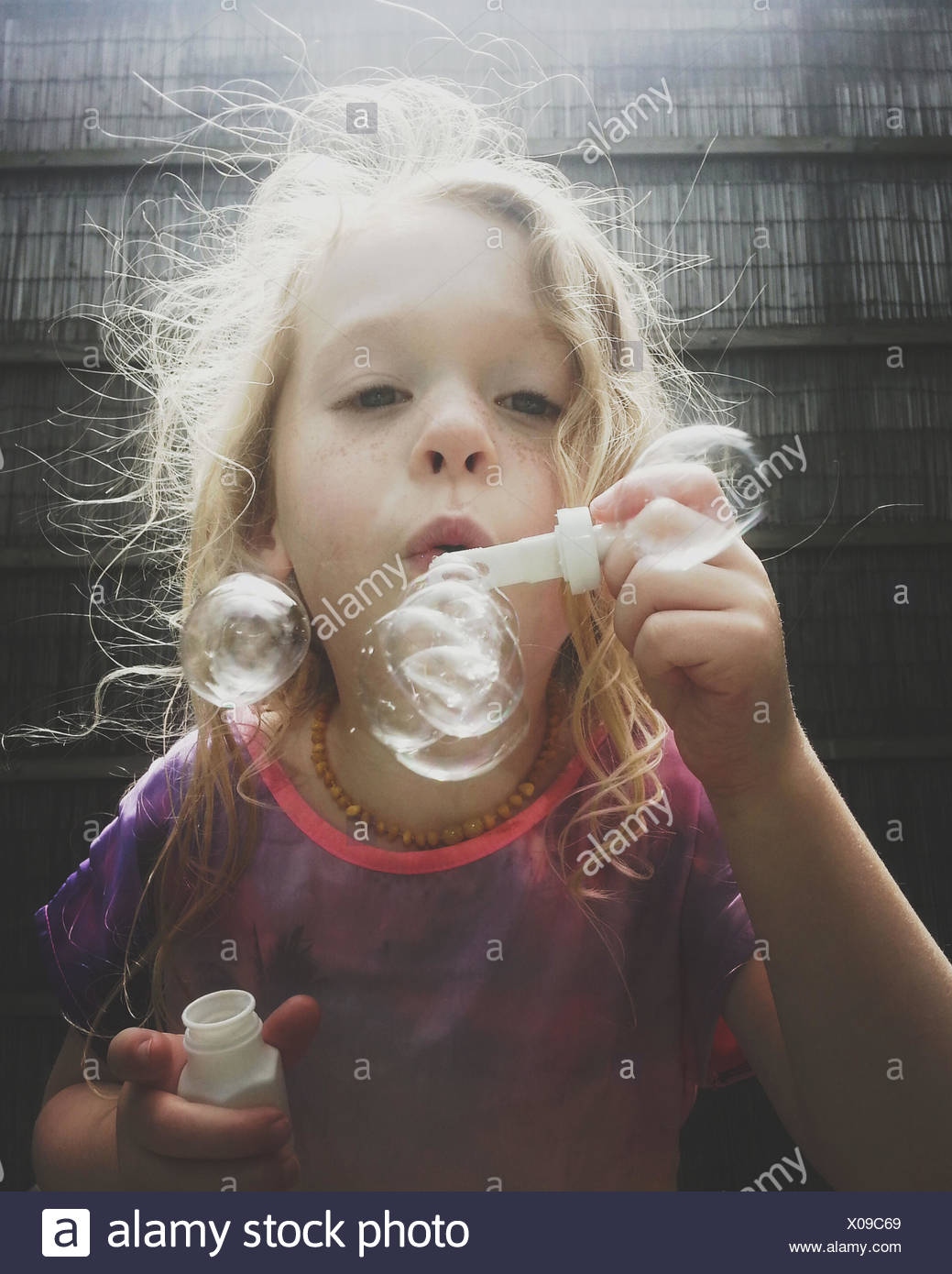 Portrait of a Girl blowing soap bubbles - Stock Image
