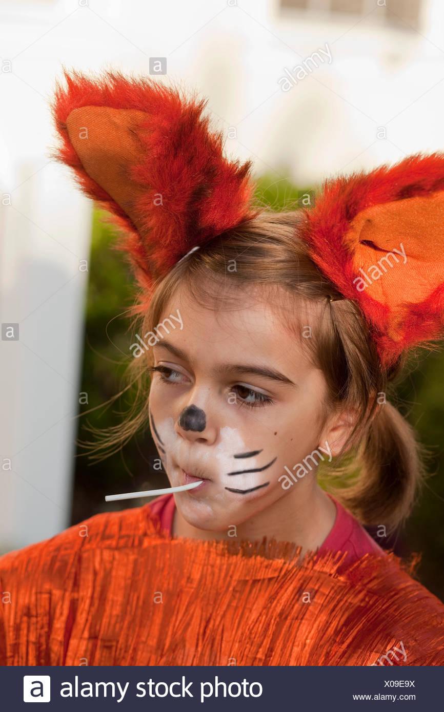 Little girl in fox costume sucking on lollipop & Little girl in fox costume sucking on lollipop Stock Photo ...