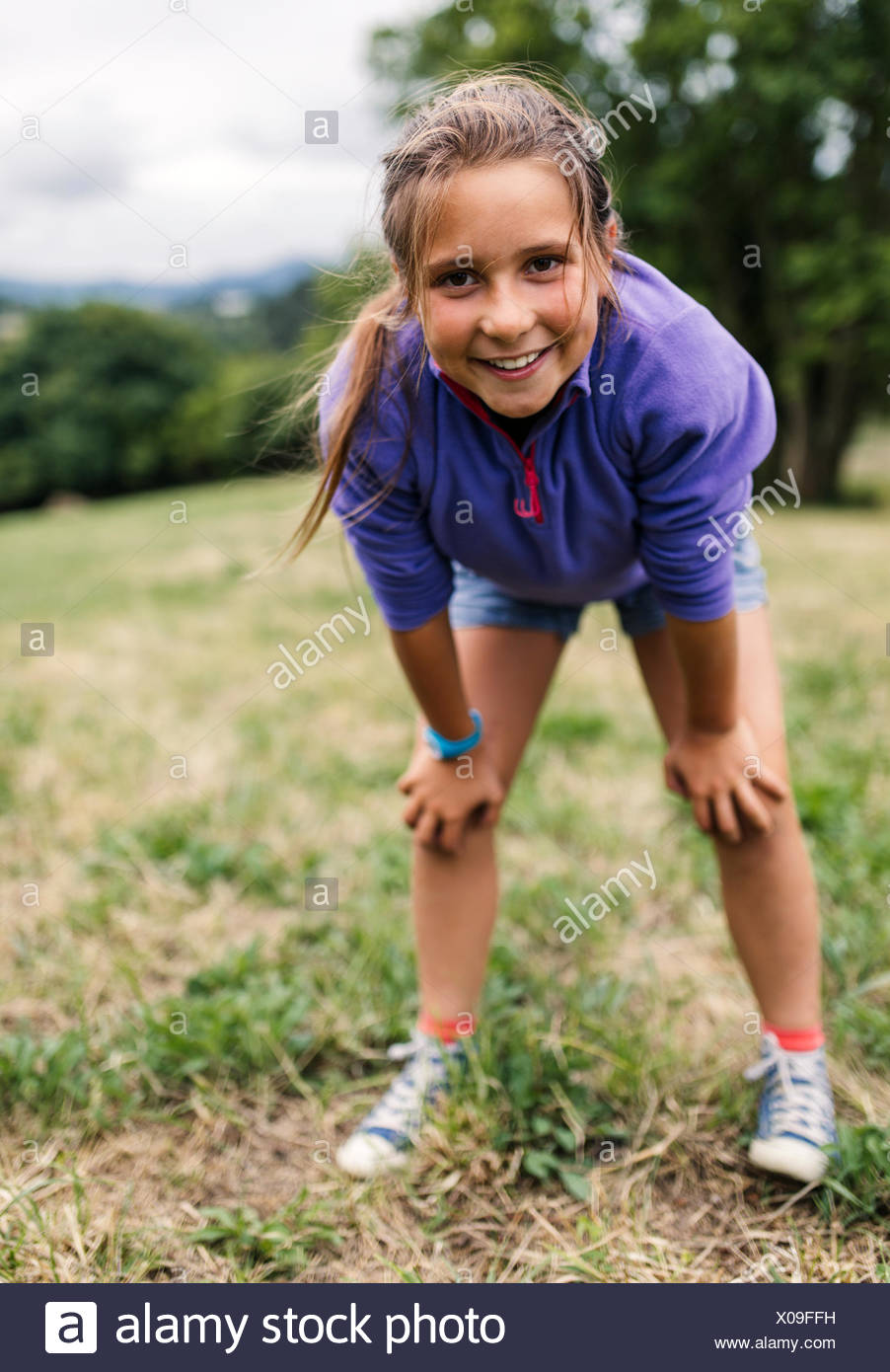 Portrait of girl standing on a meadow looking at viewer - Stock Image