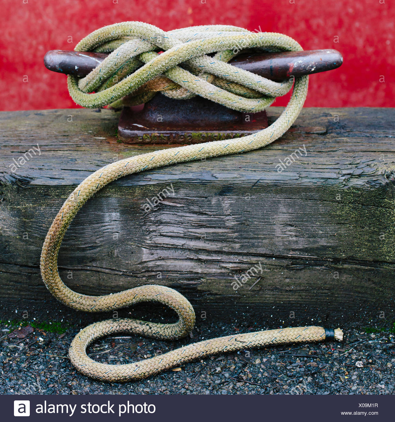 Close up of a wharfside mooring cleat with a fishing boat rope tied around it. - Stock Image