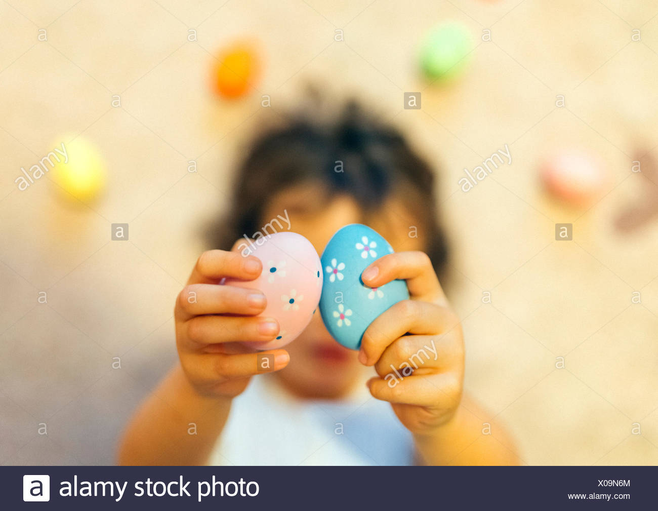 Girl's hands holding two painted Easter eggs - Stock Image