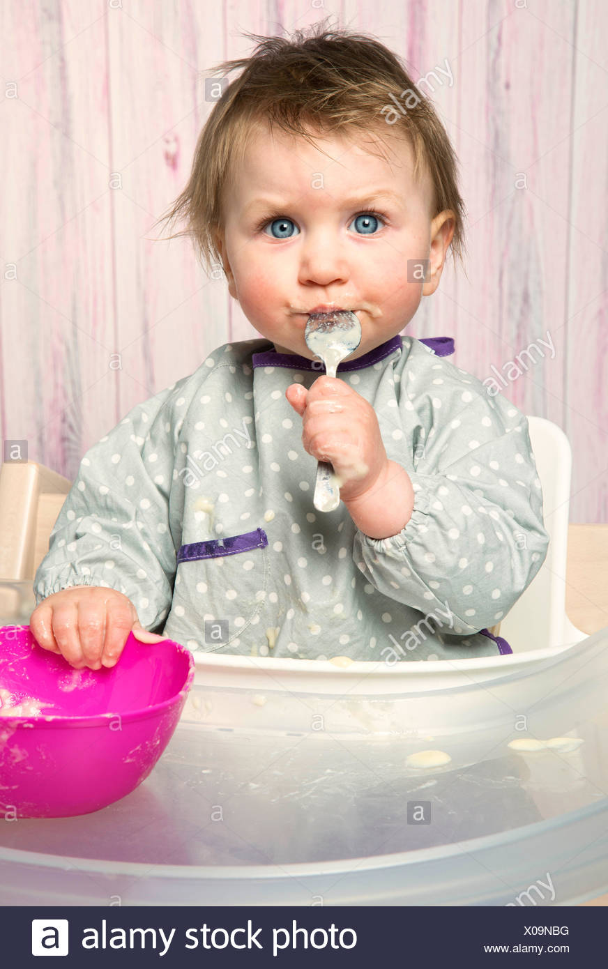 Baby, 6-12 months, mash, food, spoon, supplementary food, high-level chair, studio, portrait, - Stock Image