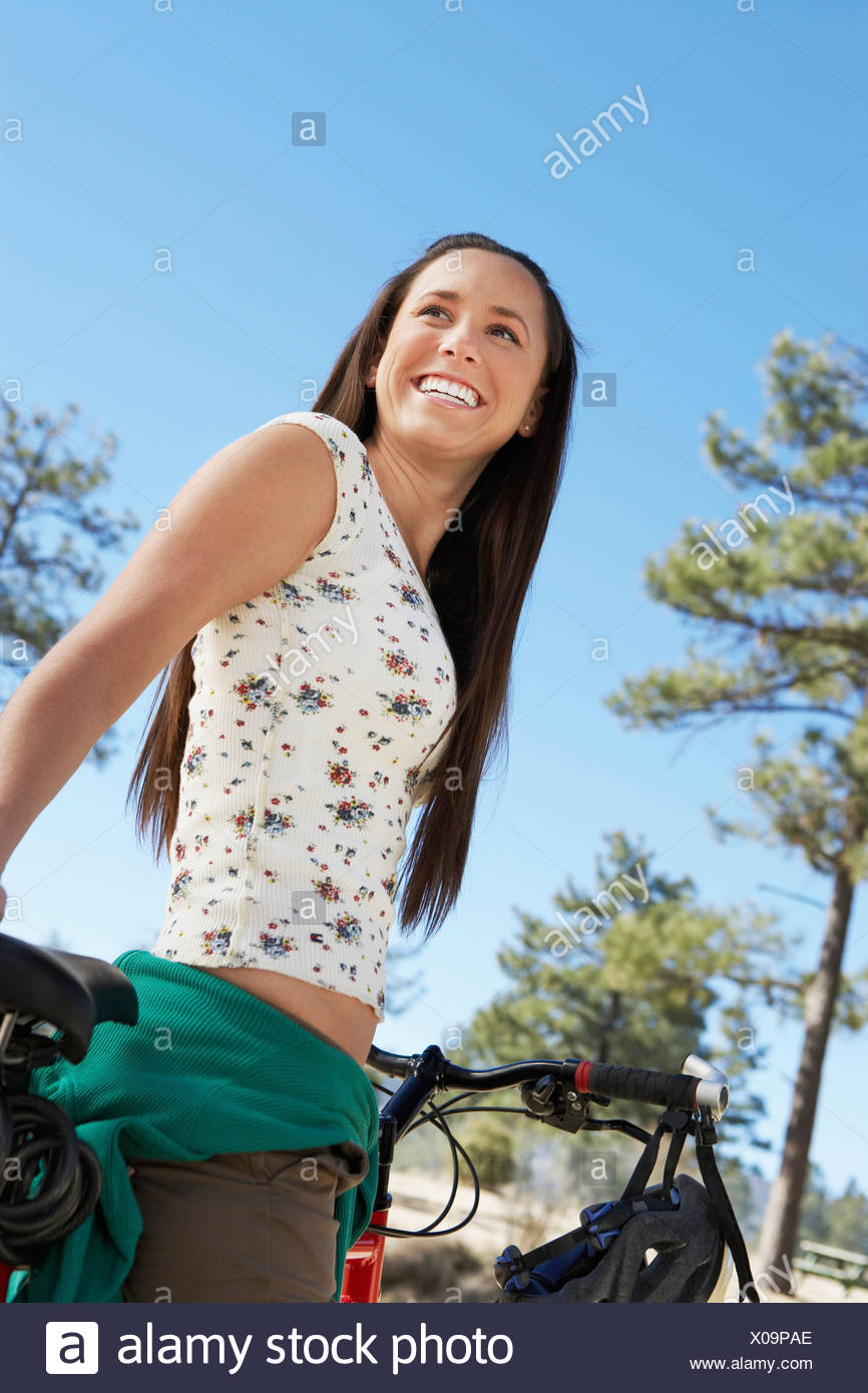 Young Woman On Mountain Bike Low Angle View Stock Photo