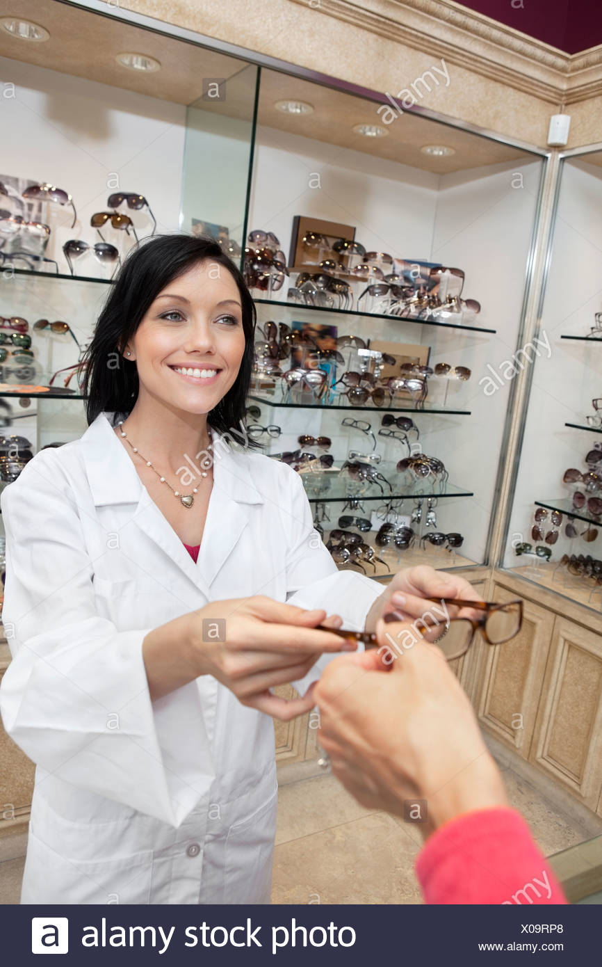 Happy eye specialist giving glasses to customer in store - Stock Image