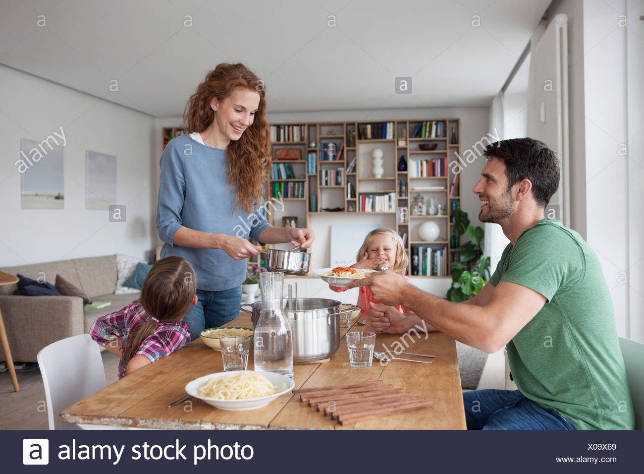 Couple with two children going to have lunch together at home - Stock Image