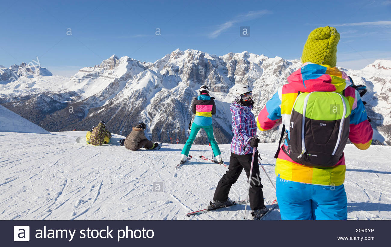 a view of a group of skiers in the Folgarida ski resort with Brenta Group in the background, Trento province, Trentino Alto Adige, Italy, Europe - Stock Image