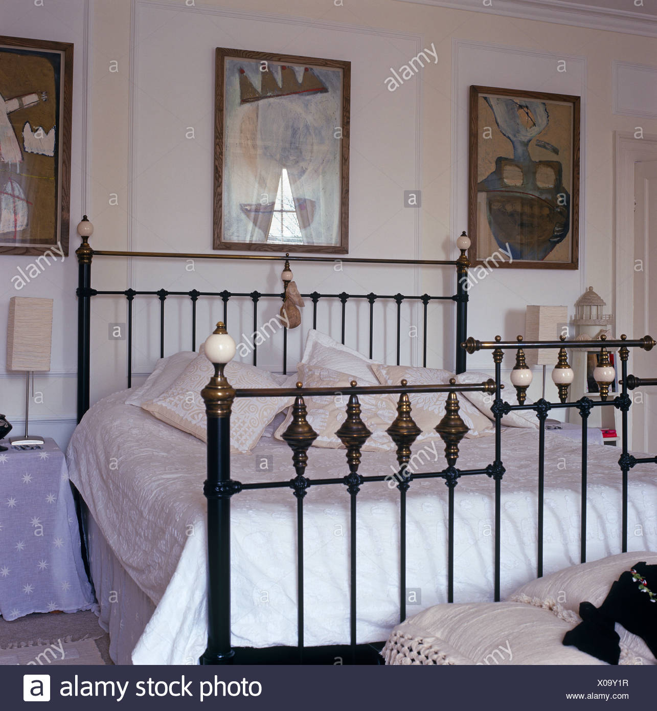 Letto Matrimoniale Ferro Battuto Antico.Three Artworks Above Antique Wrought Iron Double Bed With White