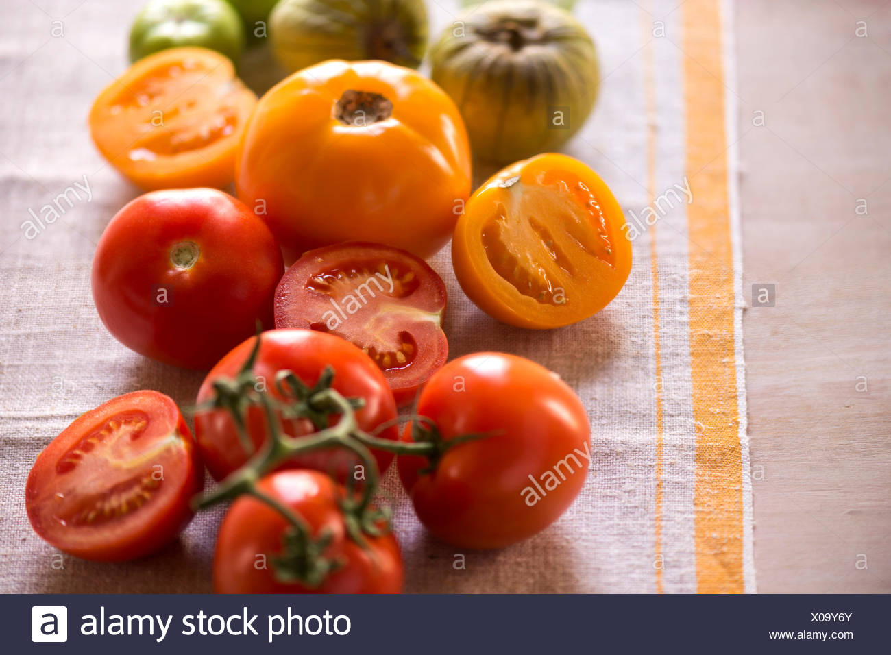 Variety of tomatoes, whole and cut, on rustic linen. Bright, summery feel. - Stock Image