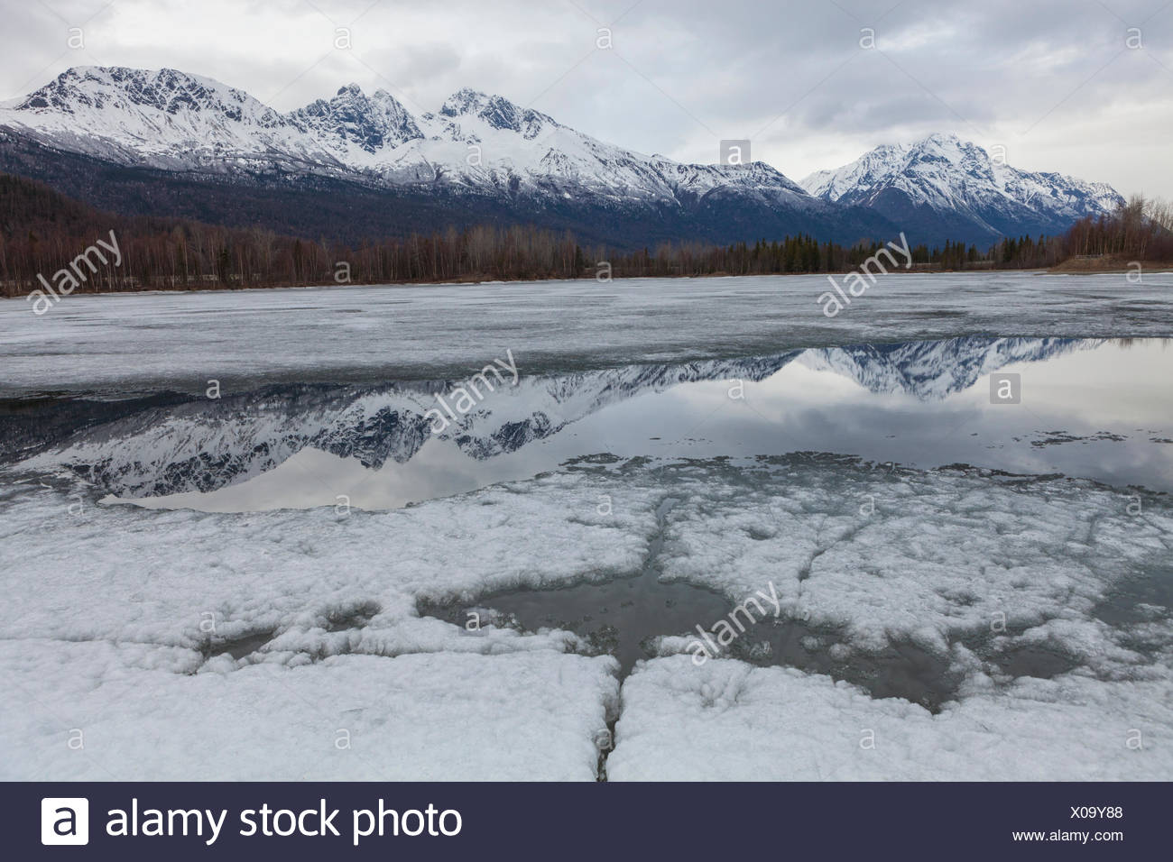 The Chugach Mountains are reflected in Mirror Lake State Wayside Park, Anchorage, Alaska. - Stock Image
