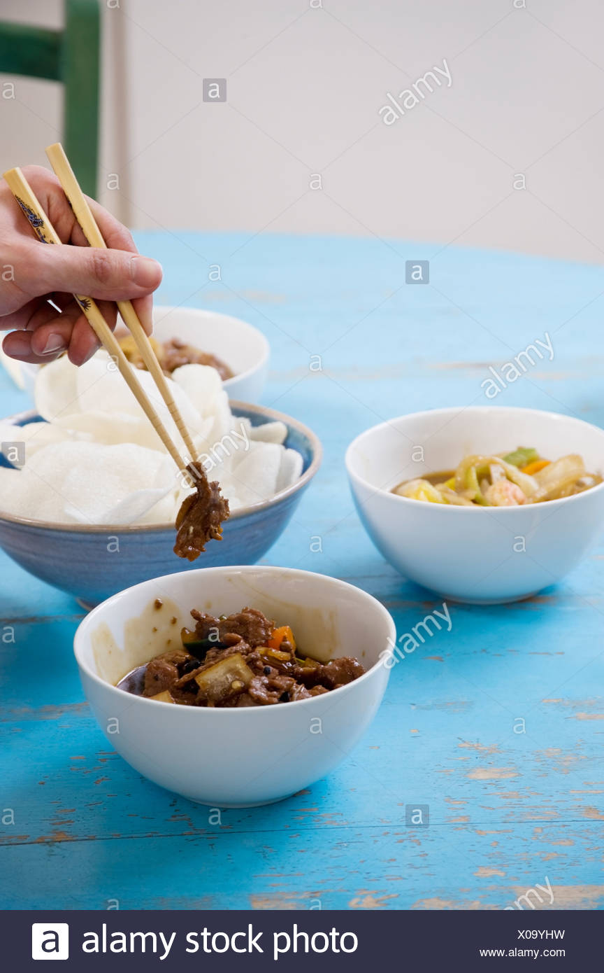 Close of human hand with chopsticks holding food - Stock Image