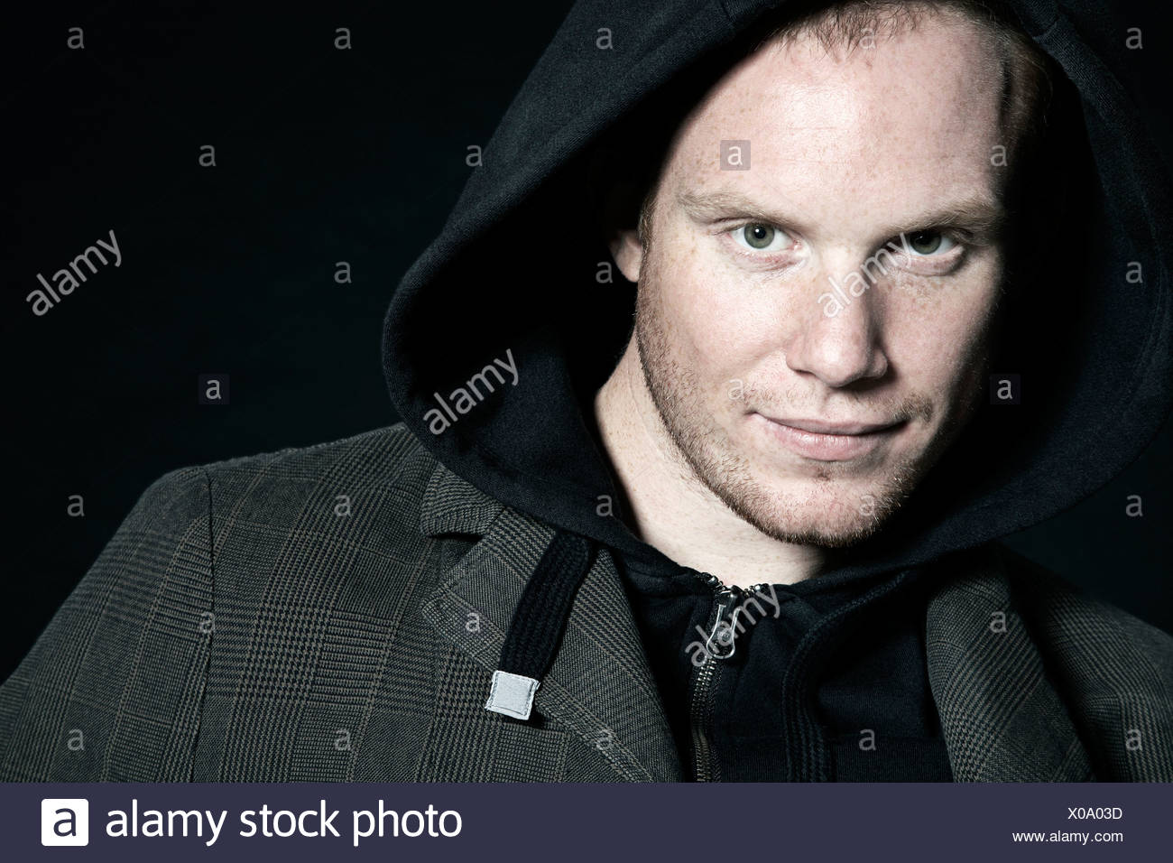 Portrait of a young man wearing a hoodie shirt looking into camera - Stock Image