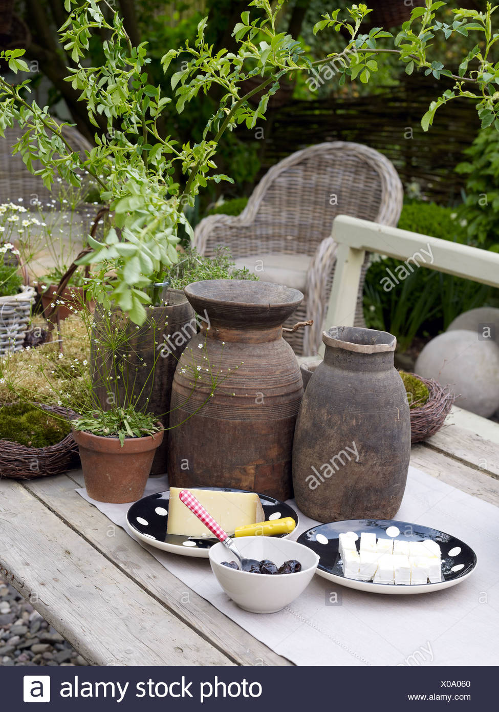 Still Life, Cheese And Olives, Surrounded By Decorative Garden Accessories  On An Old Wooden Table In A Romantic Garden