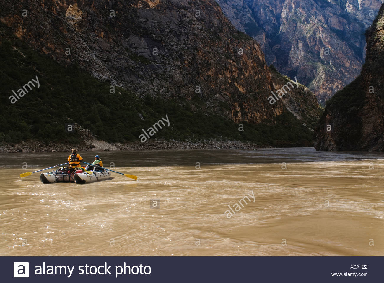 A rubber raft rows downstream during a whitewater rafting trip to