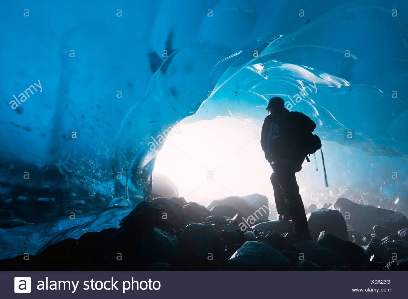 A hiker looks out the entrance of an ice cave in the Mendenhall Glacier, Juneau, Southeast Alaska, Summer - Stock Image