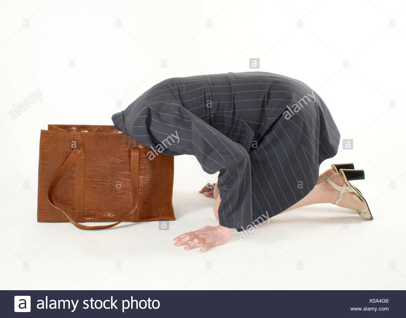 Woman sticking her head in her handbag - Stock Image