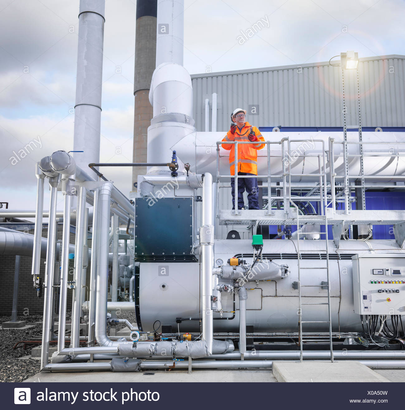 Worker standing amongst pipework of gas fired power station - Stock Image