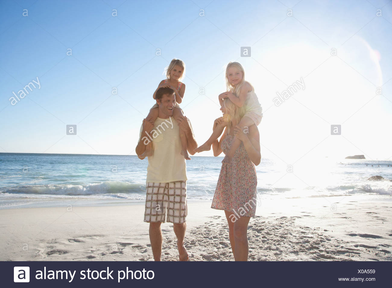 Parents carrying daughters on shoulders on beach - Stock Image