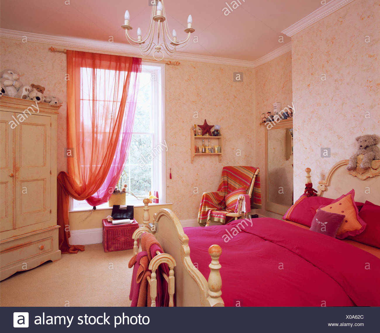 Bright pink bed cover on bed in teenage bedroom with pink ...