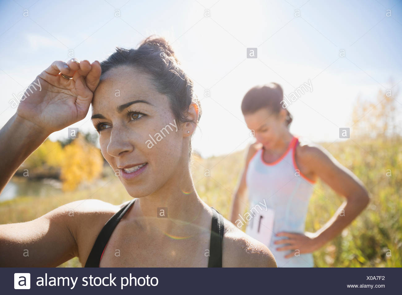 Runners resting in sunny field - Stock Image
