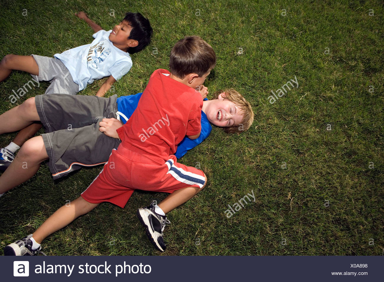 Boys Roughing Housing outside on Lawn - Stock Image