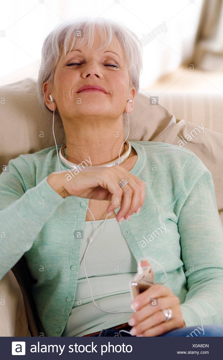 Senior woman  MP3 player, eyes shut - Stock Image