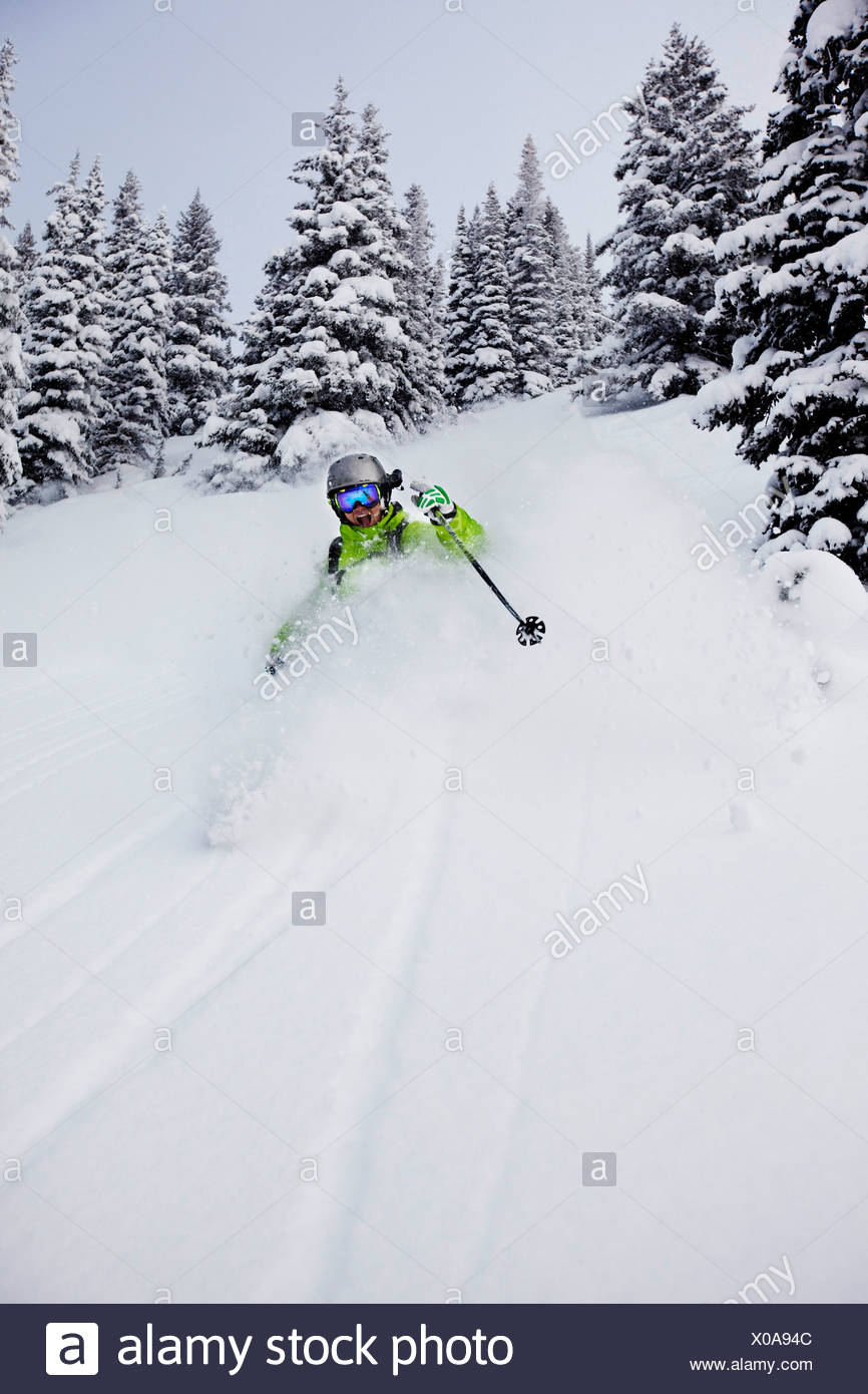 A athletic skier rips fresh deep powder turns in the backcountry on a stormy day in Colorado. Stock Photo