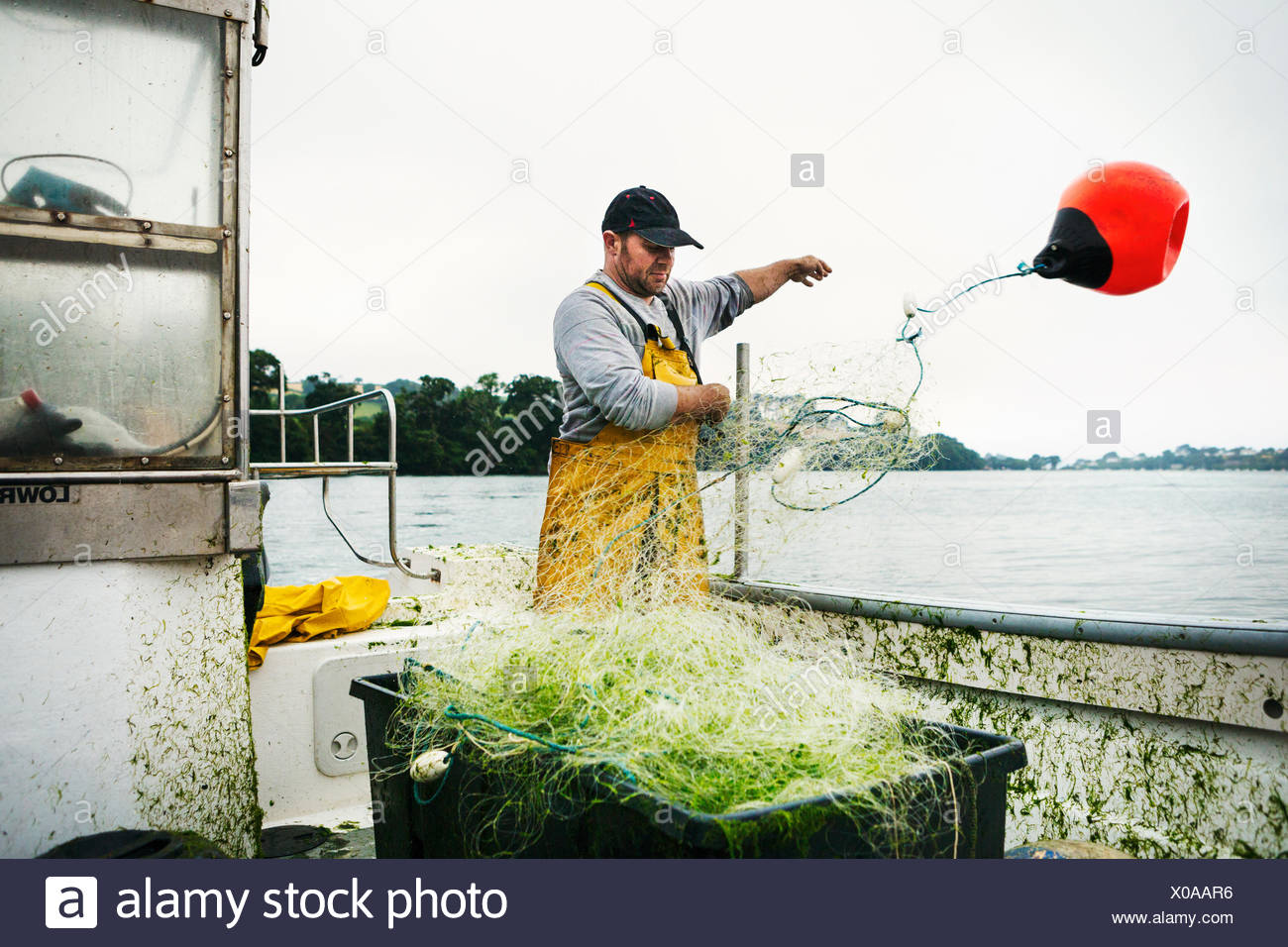 A fisherman standing on a boat throwing the floats out to spread the net over the water. - Stock Image
