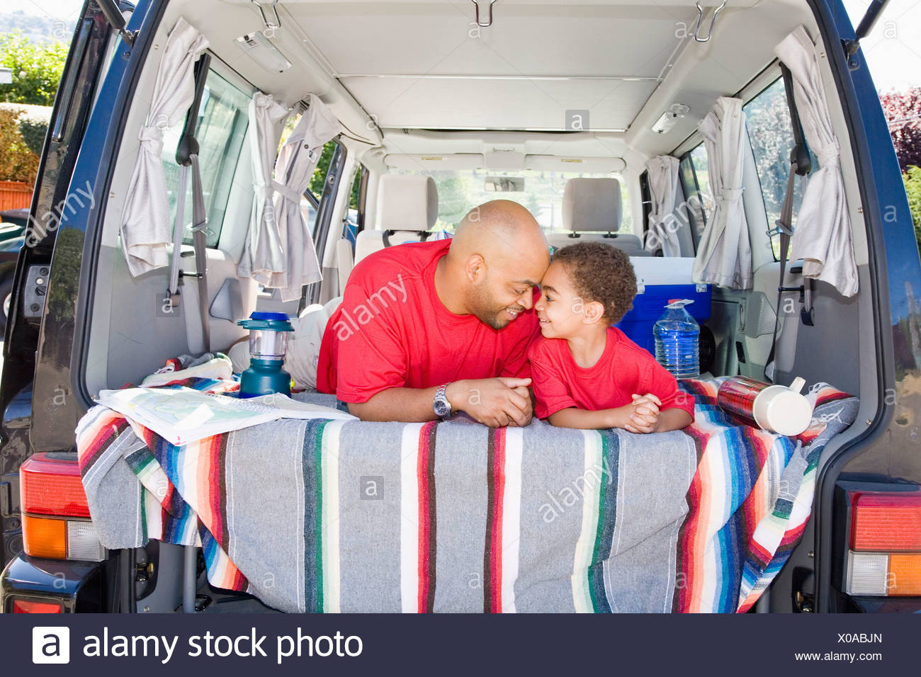 Father and son sitting in trunk of car with camping gear Stock Photo