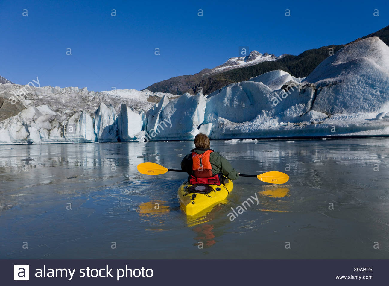 A kayaker paddles the icy waters of Mendenhall Lake with Mendenhall Glacier and Mt. Stroller White in the background, Alaska - Stock Image