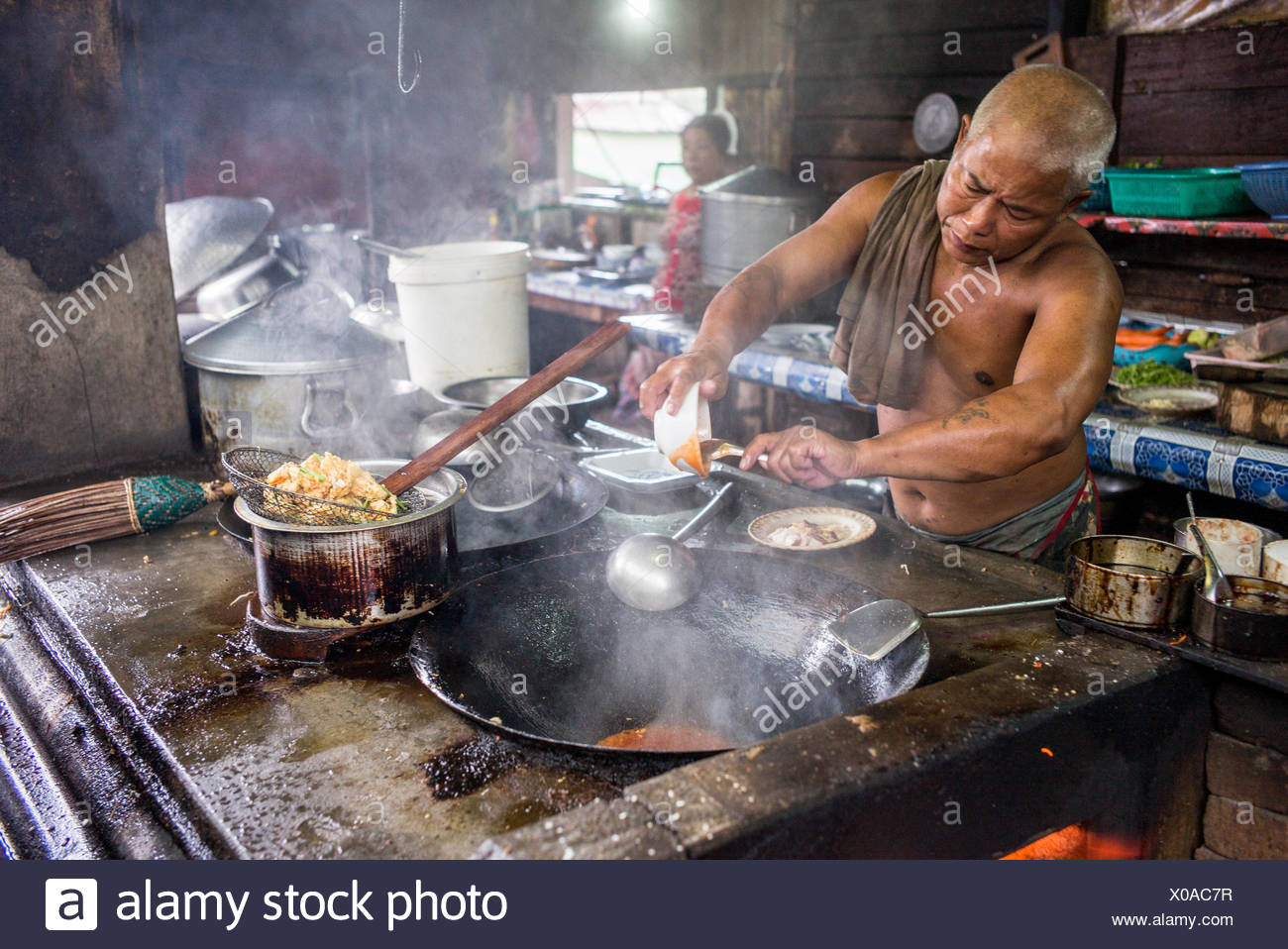 A man prepares a meal in a large, steaming pan. - Stock Image