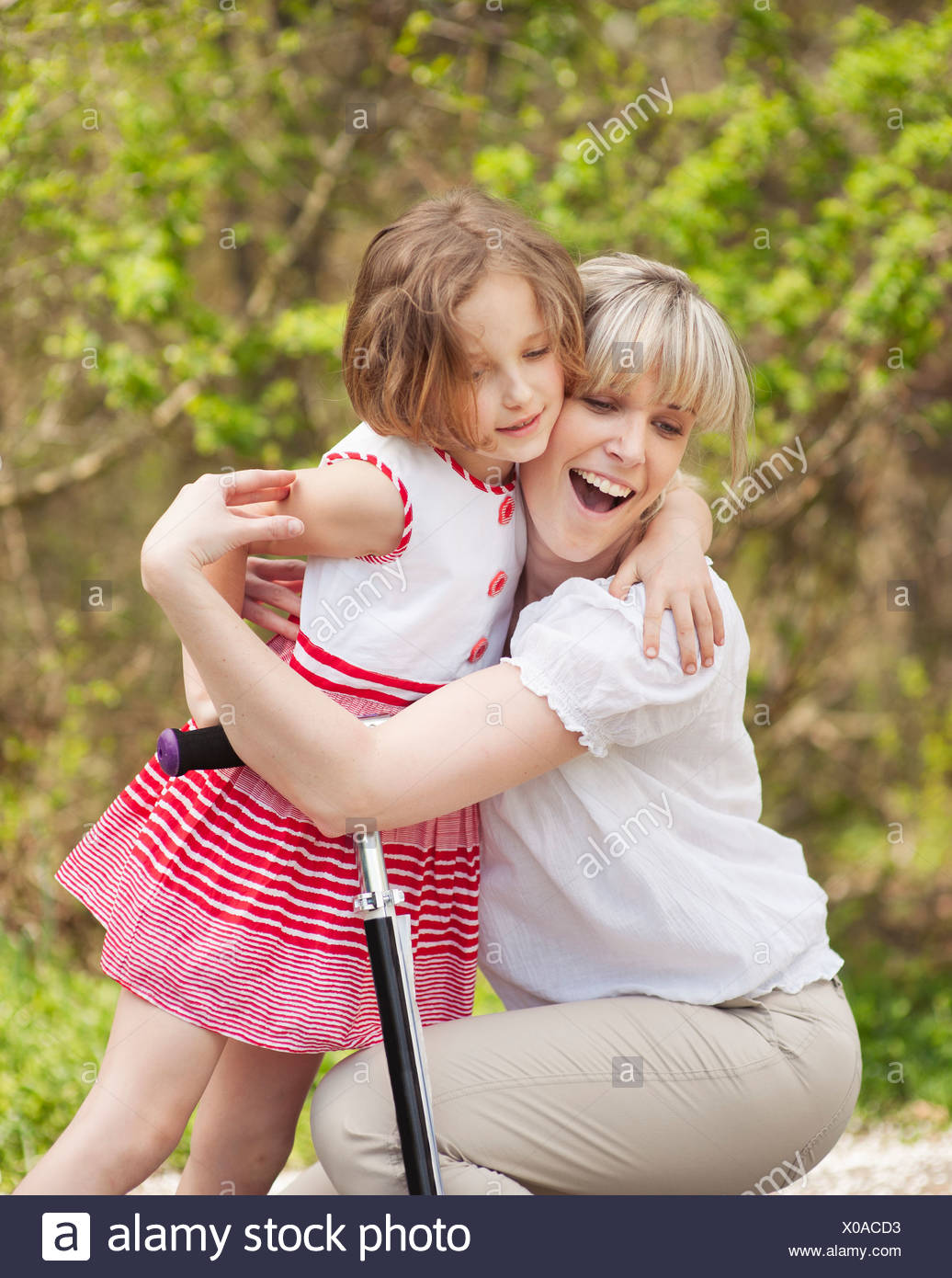 Mother and daughter hug in park with scooter - Stock Image