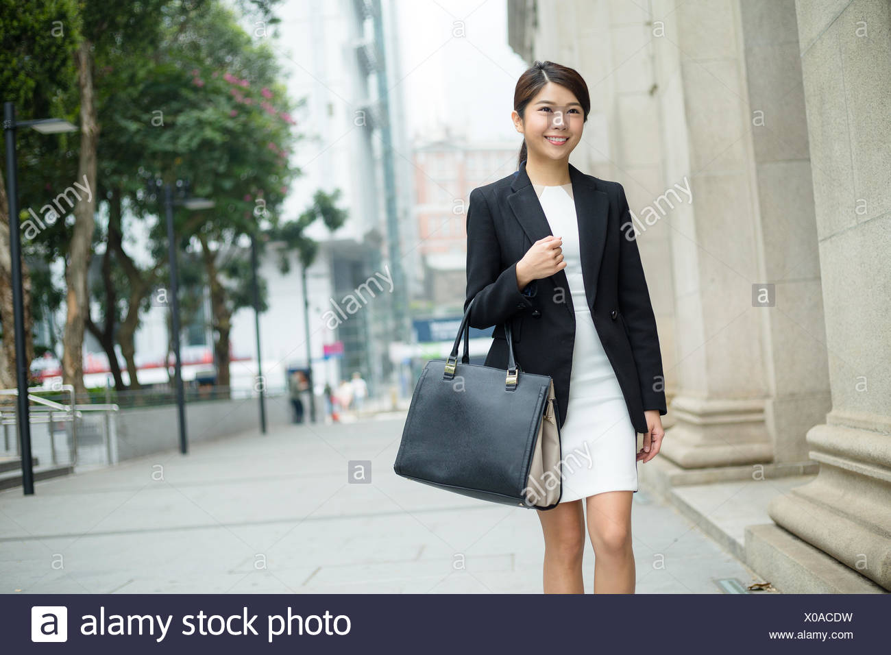 Businesswoman carry a bag and leaving office - Stock Image