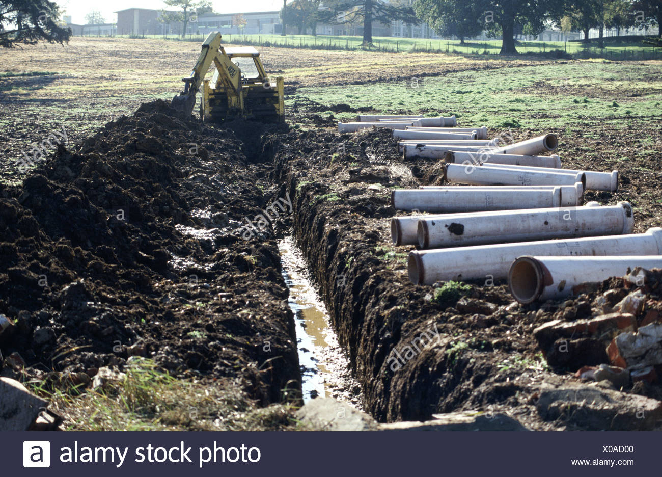 JCB Digger excavator digging trench for field drainage pipes - Stock Image