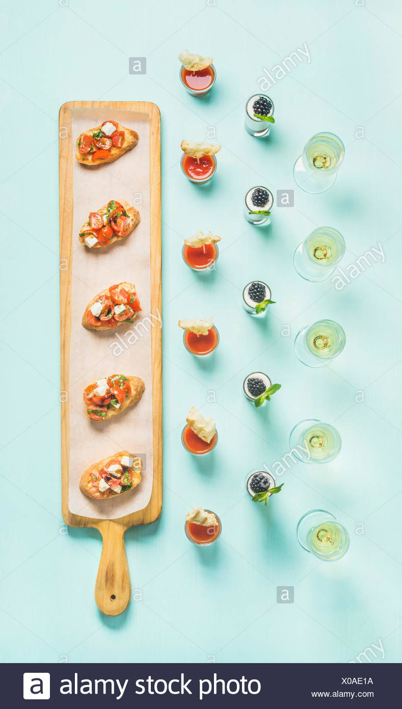 Various snacks, brushettas, gazpacho shots, desserts with berries and champagne on corporate event, christmas, birthday, wedding celebration over past - Stock Image