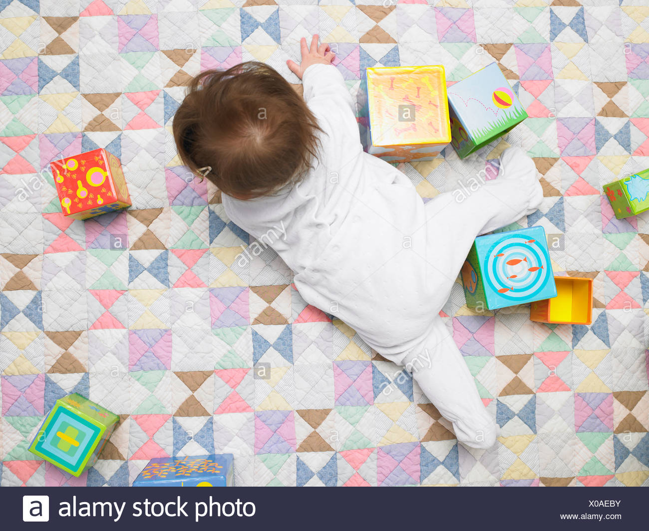 Baby with cubes on quilt - Stock Image