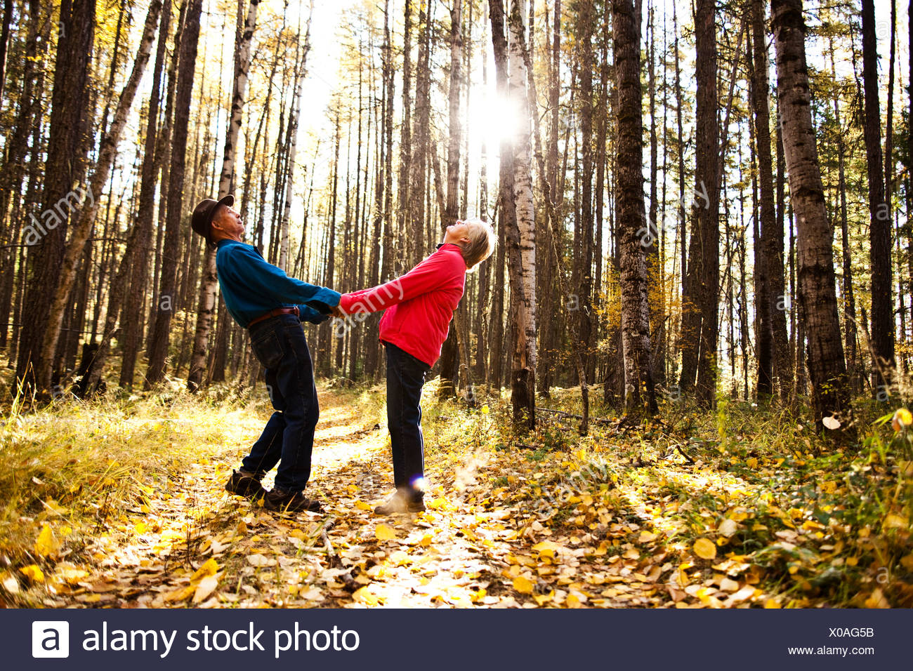 A happy retired couple laughing and smiling while on a hike through a forest during the fall in Idaho. - Stock Image