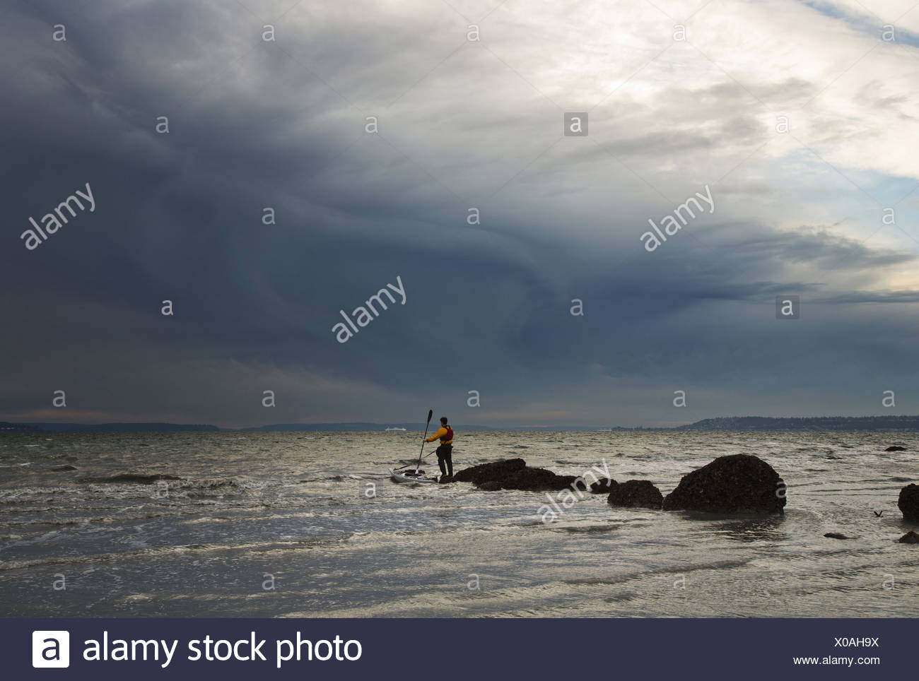 A man stands on a rock in the middle of the Puget Sound with his sea kayak floating next to him - Stock Image