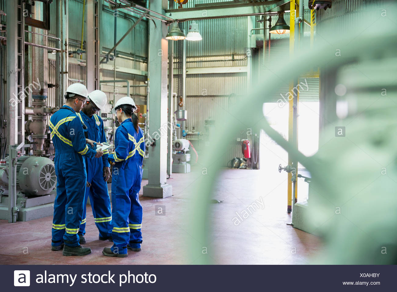 Workers reviewing paperwork in gas plant - Stock Image