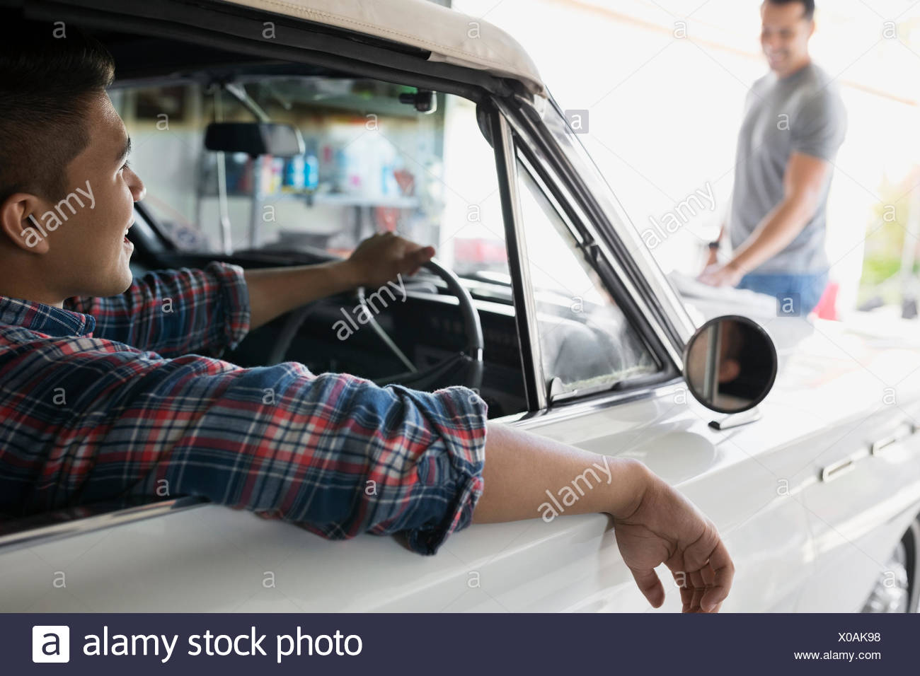 Father And Son With Vintage Car In Garage